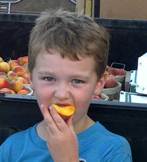Ty enjoying a fresh peach from the orchard.